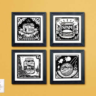 4 prints in black frames on a yellow wall.