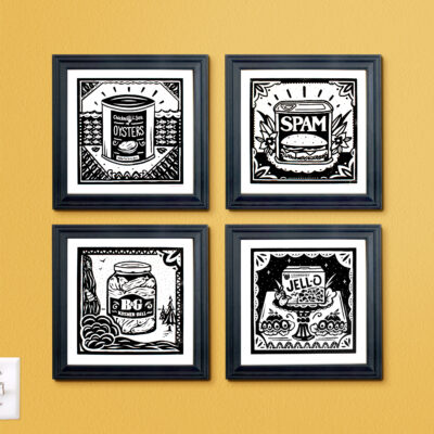 Four Screen Prints framed on a yellow wall.
